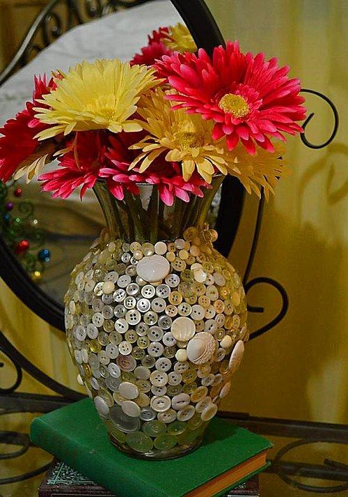 Bir bütünlük için cam eşyalar bile birlikte dekore edilmeli.  Cam tabağınızla bütünlük oluşturması için güzel çiçeklerinizi koyduğunuz vazoları da renklendirebilirsiniz. Sadece gömlek düğmelerinin bile size yardımcı olacağı bu tasarım da yok ben uğraşamam derseniz, vazonun içerisini de çiçek rengine uygun düğmelerle doldurabilirsiniz.