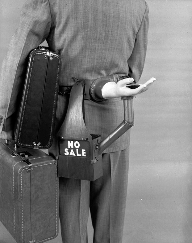 Otomatik Bahşiş İsteyici  1955 tarihli bu fotoğrafta, mucit Russell E. Oakes, bele takılması için tasarladığı icadını tanıtırken.
