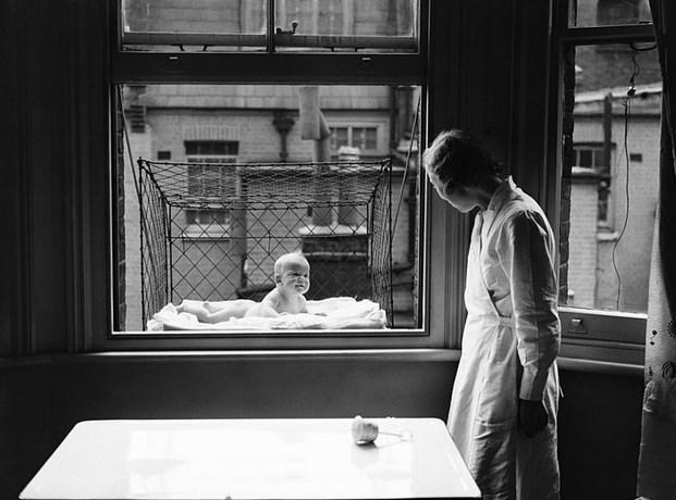 Bebekler İçin Pencere Kafesi  Temmuz 1937'ye ait bu fotoğrafta, yüksek bir apartmanın penceresine tutturulmuş kafesinde yatmakta olan bebeği ve onunla ilgilenen bakıcıyı görüyoruz.