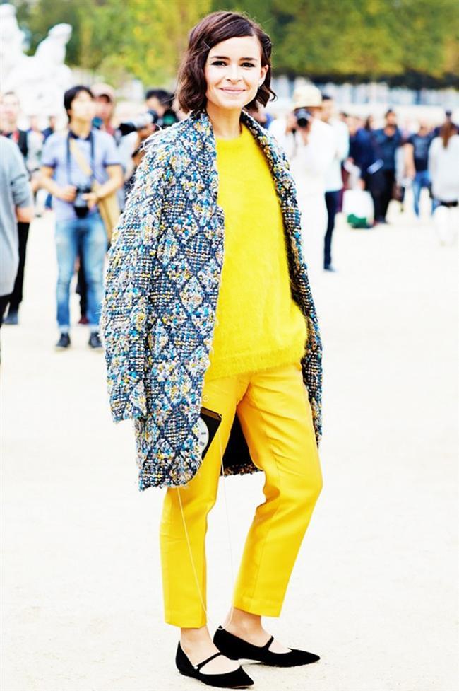Miroslava Duma  Anne olan Miroslava sarı triko kazağını saten sarı pantolon ile takımlamış ve renkli uzun ceketi ile süslemiş son olarak da düz ayakkabıları ile de bitirişini yapmış.