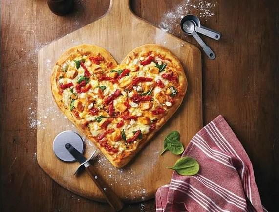 Masayı süsledik peki ya yemekler?  Evet o kadar süslü masayı yapmamızın sebebi enfes yemekler servis edecek olmamızdı. İşte bu onlardan biri. Pizzayı sevmeyen yoktur bu akşama özel pizzanızı kalp şeklinde yapabilirsiniz.  Malzemeler:  Hamuru için:  * 500 gr pizza unu * 1 tatlı kaşığı instant maya (5 gr) * 30 ml zeytinyağı * 200-230 ml su (ılık) * 70 ml süt * 5 gr tuz * 5 gr toz şeker Sosu için:  * 6 adet orta boy domates * 2 diş sarımsak * tuz * Karabiber Üzeri için:  * Kırmızı dolmalık biber * Sucuk * Çekirdeksiz yeşil zeytin * Kaşar peyniri rendesi * Kekik * Kırmızı Pul Biber