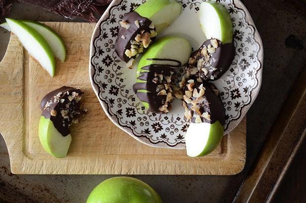 """Bitter Çikolata + Elma  Bu ikili, tatlı krizlerinizi sağlıklı olarak atlatabilmek için ideal! Bitter çikolata ve elma, potansiyel bir kalp-damar sağlığı koruyucudur. Tatlı kırmızı elmanın özellikle kabuğunda bulunan """"Kuarsetin"""" adı verilen flavonoid, anti-inflamatuar etki gösterirken, bitter çikolatadaki kakao da """"Kateşin"""" antioksidanından zengin olduğu için damar sertleşmesini önlemeye yardımcı olur. Araştırmalar bu ikilinin, vücuttaki kan pıhtılarını dağıttığını gösteriyor. Bu da elma dilimlerimizi, eritilmiş bitter çikolataya bandırarak yemek için ayrı bir sebep!  Unutmayın! Bitter çikolata, sütlü çikolatadan 6 kat daha fazla kateşin içerir!"""