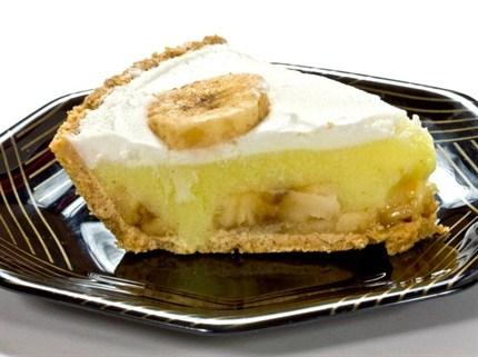 Muzlu Pasta  Malzemeler:  Kek için; 5 yumurta, 2 bardak şeker, 2 bardak un, 1 çay kaşığı karbonat, 1,5 çay kaşığı limon suyu,  6 adet muz, Krema için; Yarım kg süt, yarım bardak şeker,  2 dolu çorba kaşığı un,  1 yumurta sarısı, 1 paket vanilya, fındık büyüklüğünde margarin  Hazırlanışı:  Yumurtaları şekerle çırpın, un karbonat limon suyuyla karıştırın, yağlanmış kalıba dökün, sıcak fırında pembeleşinceye kadar pişirin. Fırından çıkarın ılıkken ortasından enlemesine ikiye kesin. Öte yandan sütü unla pişirin, kaynamaya başlayınca içine şekeri katın. un kokusu gidince ateşten indirip, vanilya, yumurta sarısı ve margarin karıştırın. Üstünün kabuk tutmaması için, zaman zaman karıştırarak soğumaya bırakın. Kekin alt yarısını servis tabağına koyun, 1 bardak ılık şerbetli su ile iyice ıslatın. Sonra 1 kat krema sürüp, 1 kat dilimlenmiş muz dizin. Üzerine kekin 2. parçasını koyup, unu da ılık şerbetli su ile ıslatın. Bütün pastayı krema ile sıvayıp, muz dilimleriyle süsleyin.