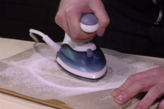 Ütünüzün çelik yüzeyini temizlemek için pişirme kağıdının üzerine bir miktar tuz döküp ütüleyin