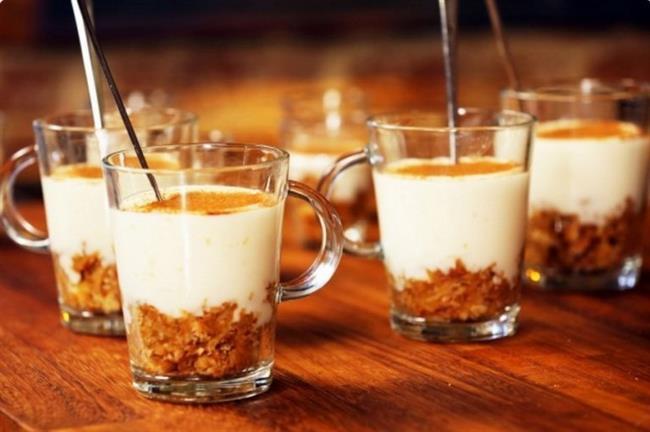Elmalı Muhallebi Kupları     Malzemeler    Muhallebi için Malzemeler   -1 litre süt  -1 bardak toz şeker  -4 yemek kaşığı un  -1 paket vanilya  -1 yemek kaşığı tereyağı   Elma harcı için Malzemeler   -3 elma  -4 yemek kaşığı toz şeker  -2 avuç kıyılmış ceviz  -1 çay kaşığı tarçın  -1 paket yulaflı bisküvi  Yapılışı   Elmaların kabuklarını soyup ince rendeleyin. Geniş bir tavaya rendelediğiniz elmaları alın ve üzerine toz şekeri ilave edin. Kısık ateşte yumuşayıncaya kadar pişirin. Elmalar yumuşayınca cevizi ve tarçını ekleyip karıştırın. Ocaktan alıp bisküvileri ekleyip soğumaya bırakın. Elmalar soğurken tencereye sütü koyun. Şekeri, unu ve vanilyayı ekleyerek orta ateşte karıştırarak koyulaşıncaya kadar pişirin. Muhallebi koyulaşınca ateşten alın. Parlaklık versin diye 1 yemek kaşığı tereyağı ekleyip karıştırarak erimesini sağlayın. Soğuyan elmaları kuplarınızın dibine pay edin. Üzerlerine muhallebi ekleyin. Oda sıcaklığına gelince buzdolabına alarak soğutun. Soğuyunca üzerine iri çekilmiş ceviz serpiştirip nane yapraklarıyla süsleyerek servis yapın.