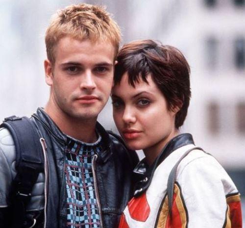 """O sırada Angelina Jolie ise ilk Hollywood filmi olan Hackers'da Jonny Lee Miller ile tanıştı.  20'li yaşlarına kadar kötü bir uyuşturucu geçmişi olan Jolie, Miller için """"Beni karanlık günlerimden uzak tutuyor."""" diyordu.  1996 senesinde, yani Brad Pitt'in Gwyneth Paltrow'a evlilik teklifi ettiği sene, Angelina ilk kez dünya evine girdi. Düğününde siyah deri bir pantolon giyen oyuncu, üzerine ise kendi kanıyla damadın adını yazdığı bir tişört giydi. Fakat bu evlilik sadece 3 yıl sürdü. Güzel oyuncu ve İngiliz aktör, 1999 yılında boşandı."""