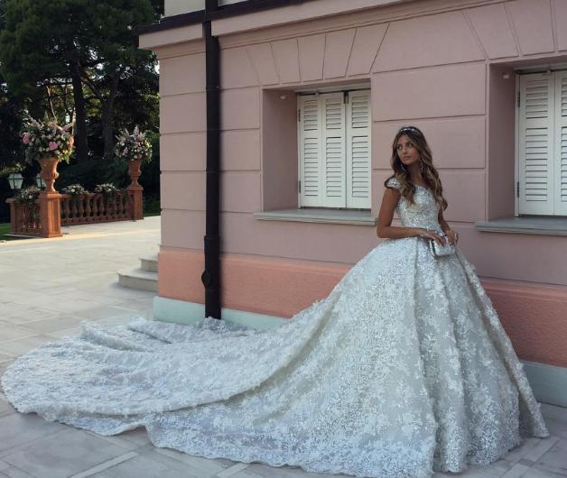 """21 yaşındaki Elena ile yine zengin bir işadamı olan Alikhan Mamakaev'in 25 yaşındaki oğlu Bek Ali Han Mamakaev'in düğünü son derece görkemliydi. Üzeri taşlarla ve işlemelerle süslü uzun kuyruğuyla dikkat çeken gelinliğin bedeli 20 milyon Rus Rublesi yani 242 bin Sterlin.    <a href=  http://mahmure.hurriyet.com.tr/foto/magazin/2016-yilina-damgasini-vuran-25-dugun_41095 style=""""color:red; font:bold 11pt arial; text-decoration:none;""""  target=""""_blank""""> 2016 Yılına Damgasını Vuran 25 Düğün!"""