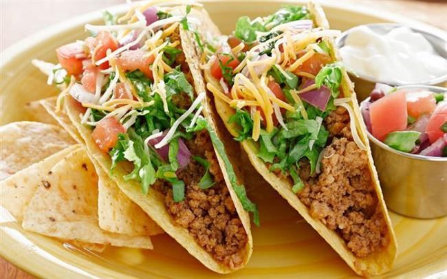 Taco  Malzemeler:  1 soğan 2 diş sarımsak 250 g kıyma 1 kırmızı kapya biberi Yarım çay bardağı dilimlenmiş jalepano biberi 1 çay bardağı konserve mısır 1 çay bardağı Meksika fasulyesi Tuz Karabiber Kırmızı toz biber Taco ekmeği  Hazırlanışı:  Yemeklik doğradığınız soğanı ve ezdiğiniz sarımsağı zeytinyağında pembeleşinceye kadar soteleyin. Kıymayı ilave edin. Kıymanın rengi dönmeye başlayınca ince doğradığınız kırmızı kapya biberi, jalepano biberi, konserve mısır ve Meksika fasulyesini ilave edin. Tuz ve karabiberle tatlandırın. Sebzeler yumuşadığında ocaktan alın. Tacoları yağlı kağıt serili bir fırın kabına alın. Arasına kıymalı harçtan koyup çedar peyniri serpin. Önceden ısıtılmış 200 derece fırında peynir eriyene kadar pişirin. Sıcak servis yapın.