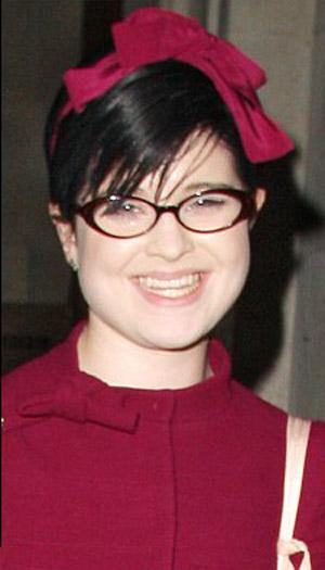 Taktığı bordo renkli gözlüklerle, Betty Suarez karakterini canlandıran America Ferrera'ya tıpatıp benzeyen Kelly Osbourne.