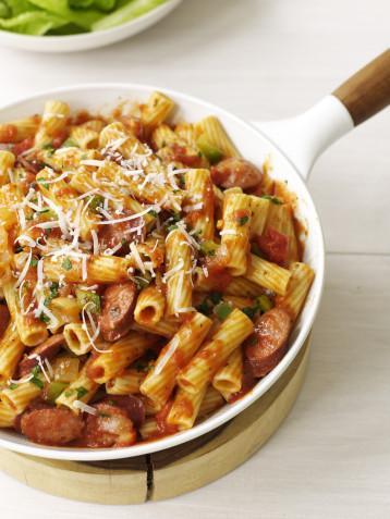 Fırında Sosisli Makarna  Malzemeler:  • 500 gr spagetti • 1 yumurta • 1 su bardağı rendelenmiş dil peyniri • 500 gr. sosis • 1 su bardağı taze mantar • Yarım su bardağı soğan • 1 diş sarmısak • 200 gr. domates taze yada küp şeklinde konserve edilmiş • Yarım su bardağı domates suyu • 1 tatlı kaşığı karışık kuru kekik, nane, fesleğen • 2 yemek kaşığı parmesan  • Kırmızı biber • Tuz, karabiber  Hazırlanışı:  Spagettileri pakette yazıldığı şekilde fakat tuz ve yağ koymadan haşlayıp süzün. Yumurta beyazı ile karıştırın. Yuvarlak bir turta kabını yağlayıp spagettileri içine dökün. Kaşıkla bastırarak düzeltin. Üzerine rende dil peynirini serpin. Sosisleri küçük küpler halinde doğrayın. Sarımsağı dövün. Soğanı,mantarı ve domatesi küçük küçük doğrayın. Orta boy bir tavada domates, domates suyu, sosis, mantar, soğan ve sarımsağı karıştırarak pişirmeye başlayın. Sosisler pişince içine karışık kuru otları, tuz, karabiber ve kırmızı biberi ekleyin. Makarnaların üzerine dökün. Üzerini aliminyum folyo ile kapatıp 175 derece ısıtılmış fırında 25-30 dakika pişirin. Fırından çıkarıp üzerine parmesan dökün. 6 dilim halinda kesip servis yapın.